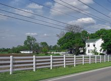Farm in countryside. Scenic view of farm and fields in countryside with fence and road in foreground Royalty Free Stock Images