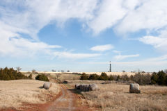 Farm and Drilling Rig. Red dirt road leads into a farm lined with round hay bales and an oil drilling rig on the horizon Stock Photos
