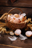 Farm eggs in wicker basket on wooden background Stock Images