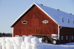 Farm, ensilage and tractor. Small red farm in wintery sweden, snow and ice, showing tractor and ensilage stock photography