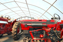 Farm equipment. Detailed side views of a tractors under a greenhouse roof for protection Stock Photo