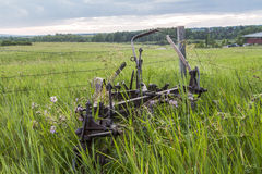 Farm equipment in a field. Farm equipment left in a field being overgrown by grass royalty free stock photo