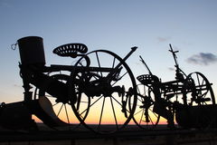 Farm equipment at sunset Stock Photos