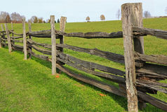 Farm Wood Fence. Aged split rail chestnut wood farm fence on Green Meadow Royalty Free Stock Photo