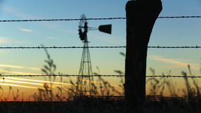 Farm Fence Rack Focus to Windmill. Pan and rack focus from some grass and barbed wire fence in the foreground to a old fashioned windmill in the background stock video