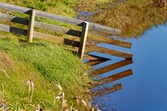 Farm fence reaching into the water stock image