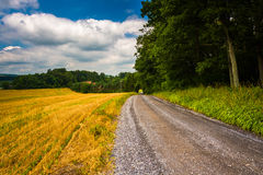 Farm field and dirt road in rural Carroll County, Maryland. Stock Photos