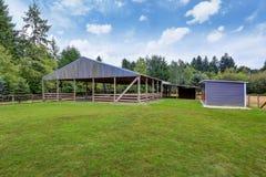 Farm field with empty horse barn stock photography