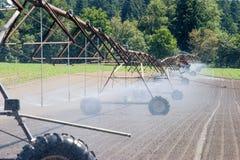 Farm field irrigation crawler. A farm field being irrigated by a irrigation crawler Royalty Free Stock Photos