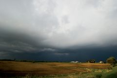 Farm field and storm. Farm field with thunder storm looming in the background Royalty Free Stock Images