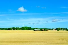 Farm fields with farmers house and wind power generators. Agrivulture concept. stock photography