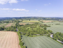 Farm fields, pastures, meadows, aerial view of english countryside . Aerial view of agriculture farm land with green wheat and ploughed fields, small village Royalty Free Stock Photos