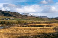 Farm at the Foot of a Mountain in Iceland on a Sunny Fall Day. Beautiful Rural Landscape in the Countryside of Iceland on a Sunny Autumn Day royalty free stock images