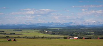 Farm on the Foothills in Alberta. A farmstead on the foothills of alberta canada with the Rocky Mountains in the background stock images