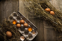 Farm fresh eggs on dark wooden table. Farm fresh eggs, cracked open in a egg container with hay on a dark wooden table Royalty Free Stock Images