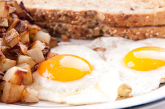 Farm fresh eggs sunny side up with home fries and whole wheat to Stock Image