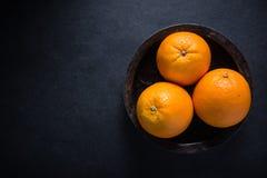Farm fresh orange fruit in rustic bowl Royalty Free Stock Photography