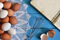 Farm Fresh Organic Eggs. A top view image of farm fresh organic eggs, wire whisk and cookbook on a bright blue background stock photos