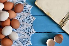 Farm Fresh Organic Eggs. A top view image of farm fresh organic eggs, wire whisk and cookbook on a bright blue background stock photography