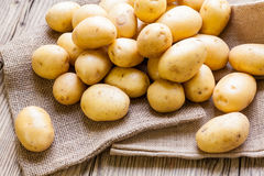 Farm fresh potatoes on a hessian sack. Farm fresh baby potatoes displayed on a hessian sack on a rustic wooden table at farmers market, a healthy nutritious root royalty free stock photo