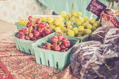 Farm fresh grapes and vegetables and lettuces on display at farmers market harvest festival Royalty Free Stock Photography