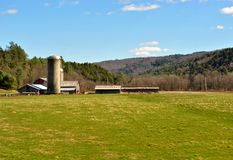 Country Living in Vermont. A farm in a freshly mowed field in Vermont with mountains in the background Royalty Free Stock Images