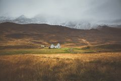 Farm in front of a empty mountain range with fog and snow. Lovel. Y landscape and tough nature in Iceland Stock Photos