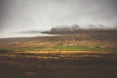 Farm in front of a empty mountain range with fog and snow. Lovel. Y landscape and tough nature in Iceland Royalty Free Stock Image