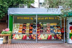 Farm fruit shop on the street of the city on a Sunny summer day. Sold Pineapples, peaches, berries, melons, watermelons royalty free stock images