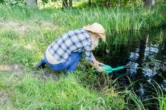Farm gardener girl draw water from pond Stock Photo