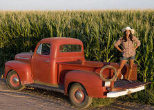 Farm Girl. A beautiful woman on the farm with her old pickup truck Stock Photo