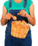 Farm Girl with Basket of Eggs. Closeup of a Farm Girl putting a fresh picked egg into a basket held in front of her body. Girl is wearing overalls and a t-shirt Stock Photos