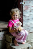 Farm girl holding an armload of kittens. An adorable little farm girl in pink overalls holds an armload of new baby kittens born in the family barn Stock Photos