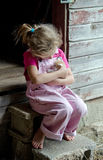 Farm girl holding a kitten. An adorable little farm girl in pink overalls holds a new baby kitten in the family barn Stock Image