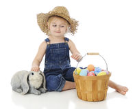 A Farm Girl`s Easter. An adorable preschool `farm girl` happily petting a bunny while admiring a fruit basket full of colorful eggs.  On a white background Royalty Free Stock Photos