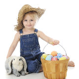 A Farm Girl's Easter. An adorable preschool farm girl happily sitting by a bunny and fruit basket full of colorful eggs.  On a white background Royalty Free Stock Photography