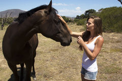 Farm girl speaking horse. Farm girl meeting and greeting a horse in a meadow Stock Image