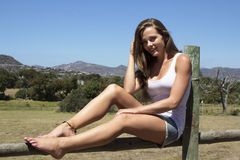Farm girl waiting. Caucasian farm girl posing on a wooden field fence Stock Photography