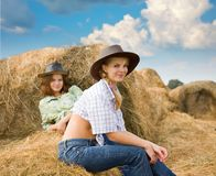 Farm girls restings on  hay Royalty Free Stock Image
