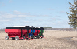Farm grain trailers. Red,blue and green coloured farm grain trailers as pulled by tractors in a field Stock Photos