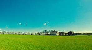 Farm in green countryside. Scenic view of rural Polish farm in countryside with green field in foreground Stock Photography