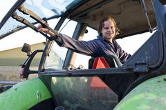 Farm hand in a tractor. Farm hand looking out the rear window of a tractor, hodling the lever Stock Photo