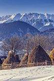Farm with haystacks in winter. Winter rural landscape with traditional Romanian farm with sheep pen and haystacks near Piatra Craiului massif in Magura village Stock Photo
