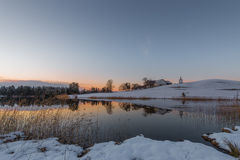 Farm on hill at lake in winter while orange sky. Of sunset Royalty Free Stock Images