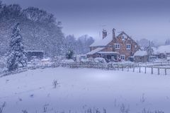 Farm house cottage during Christmas winter snow storm Royalty Free Stock Photos