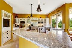 Farm house interior. Luxury kitchen room with big island and gra. Farm house interior. Luxury kitchen room in bright yellow color with big island and granite top Royalty Free Stock Photos