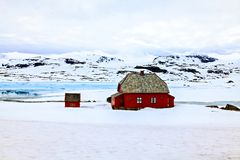 Farm house on the shore of a frozen lake Stock Images