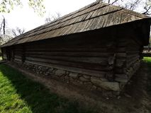 Farm house - walls of wooden barns. And foundation of river stones stock image