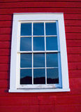 Farm house window. White weathered window against red painted Michigan farm house with reflected blue sky in window pain royalty free stock photos