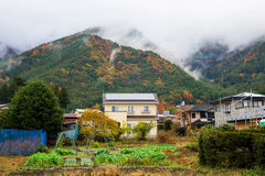farm and houses near mountain with autumn color Stock Images